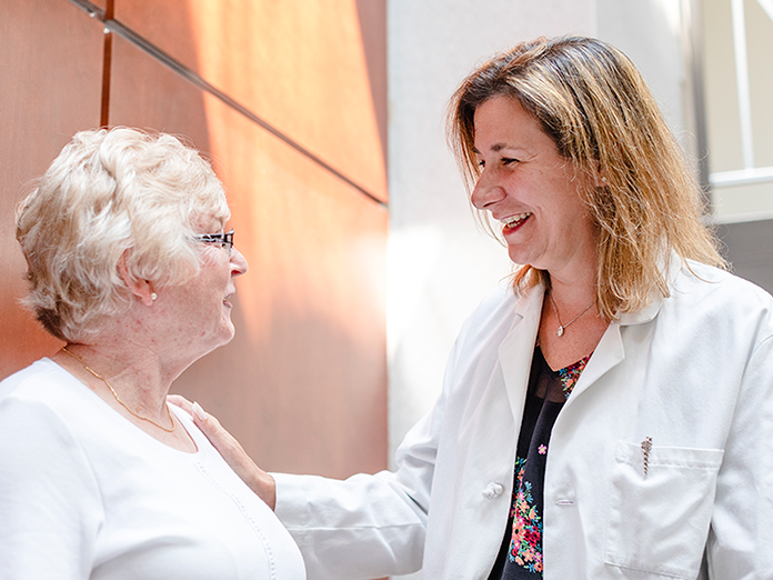A pharmacist smiling at a senior woman