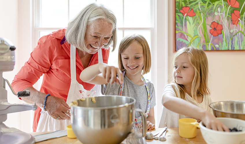 Older woman in kitchen baking with two young girls