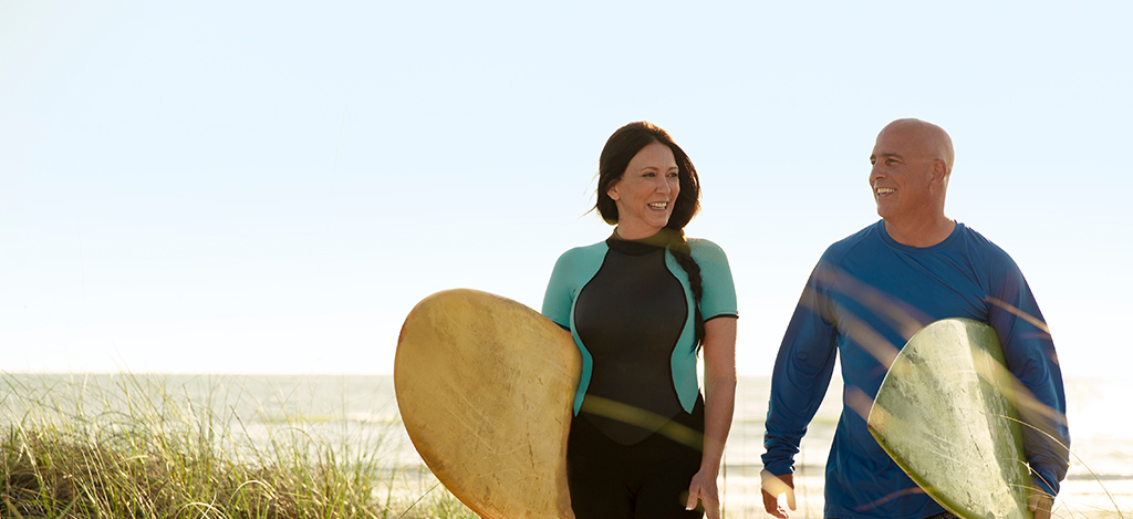 Man and woman walking with their surfboards on the beach