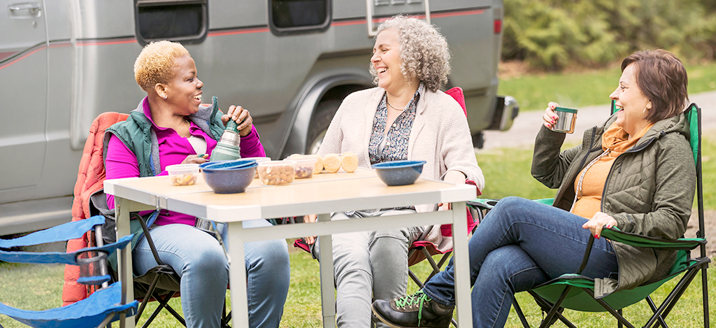 Friends talking and laughing while enjoying food at a campground