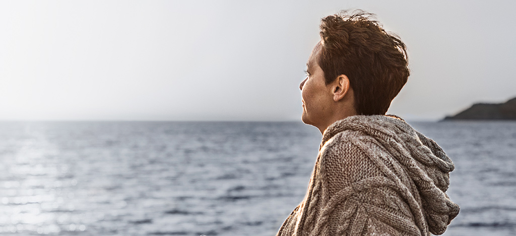 Older woman looking out at the ocean