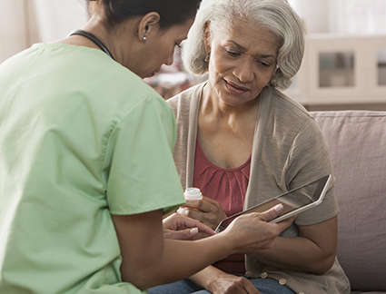 Nurse explaining to elderly patient on tablet